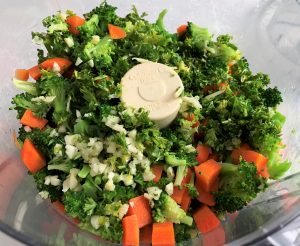 chopped broccoli, carrots, garlic and parsley in food ;processor